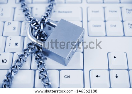 Locked chain on white computer keyboard  - stock photo