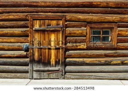 Locked door in the old log wall - stock photo