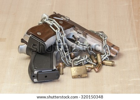 Locked Guns with chain abstract Weapon-free zone on wooden - stock photo