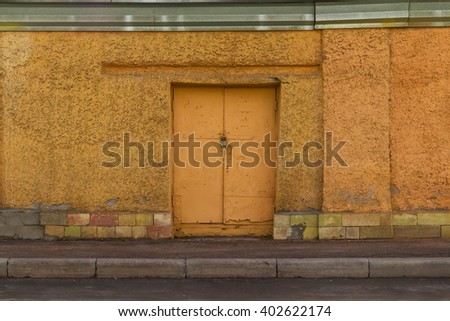 Locked iron door in yellow concrete wall front view