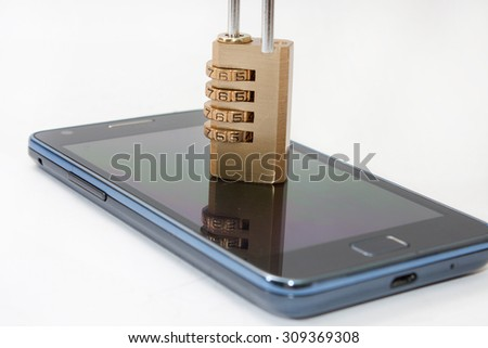 Locked mobile phone with padlock combination. - stock photo