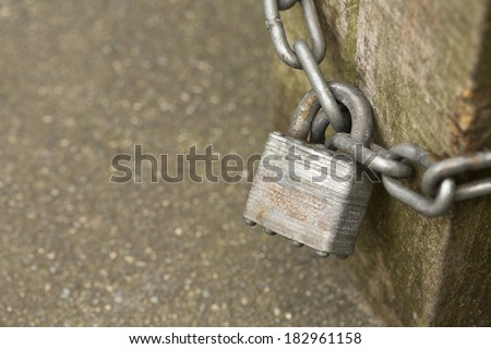 Locked padlock and chain on a wooden bench leg with copy space. Shallow depth of field - stock photo