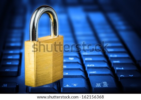 Locked padlock om a glowing blue computer keyboard useful to illustrate data security - stock photo