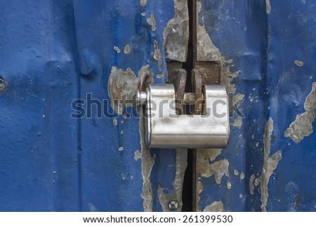 locked padlock on metal door, entrance to the warehouse - stock photo