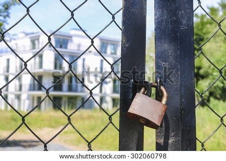 Locked padlock on the gate to the abandoned building - stock photo