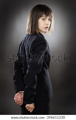 locked up business woman in handcuffs - stock photo
