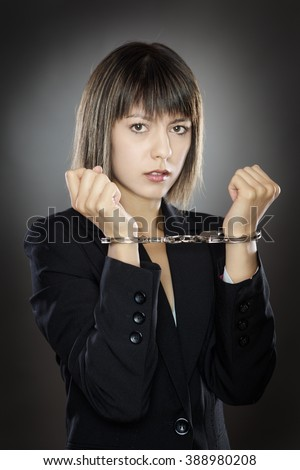 locked up business woman in handcuffs with her hands up  - stock photo