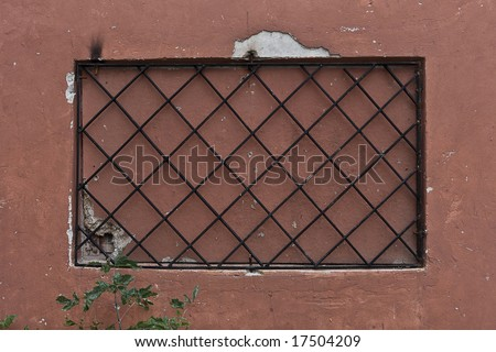 Locked window with black grate on it