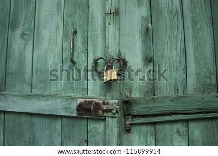 Locked wooden door with padlock - stock photo