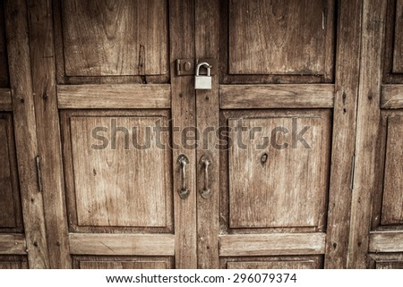 locked wooden door with silver padlock - stock photo