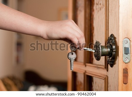Locking up or unlocking door with key in hand - stock photo