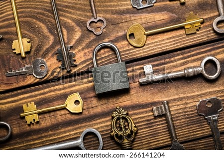Locksmith. Check-lock and different keys on wooden background concept - stock photo