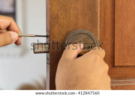 locksmith on wood door for repairing by screwdriver - stock photo