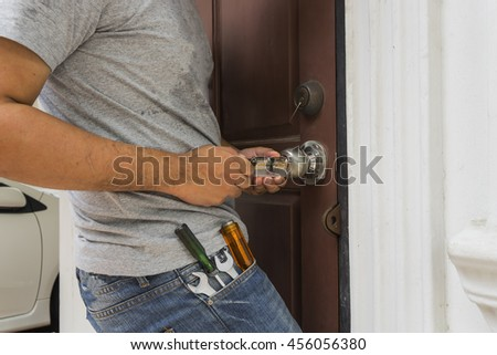locksmith try to open the door with key maker tool and screwdriver - can use to display or montage on product - stock photo