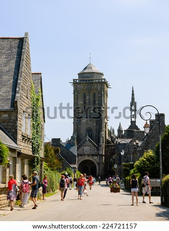 "LOCRONAN, FRANCE - JULY 23, 2014: Tourists visit medieval village Locronan and Saint Ronan church. Locronan is included in list of ""The most beautiful villages of France"""