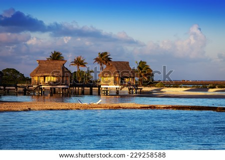Lodges over transparent quiet sea water- tropical paradise, Maldives - stock photo