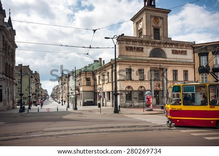 LODZ CITY, POLAND - MAY 17,  2015: A tram at the Liberty Square, Old City Hall and view of the Piotrkowska Street - stock photo