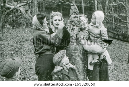 LODZ,POLAND, CIRCA FIFTIES -  unidentified family with children posing outside, in front of a dwarf statue - in Lodz, Poland, circa fifties