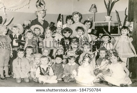 LODZ,POLAND, CIRCA 1970's: Vintage photo of group of little children and teachers posing together during a costume party in nursery school - stock photo
