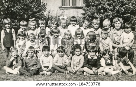 LODZ,POLAND, CIRCA 1960's: Vintage photo of group of little classmates and teacher posing together outside in front of the school - stock photo