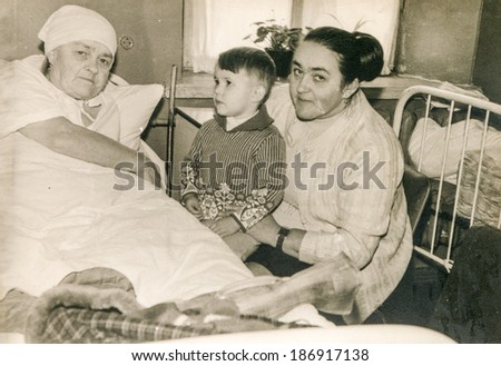 LODZ, POLAND, CIRCA 1950's: Vintage photo of mother with little son visiting bedridden grandmother in hospital