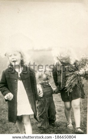 LODZ, POLAND, CIRCA 1950's: Vintage photo of three siblings walking with bunch of wild flowers