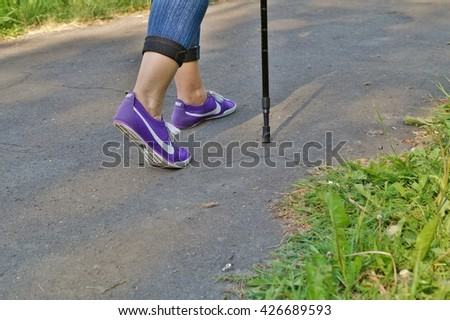 LODZ,POLAND,23 MAY 2016: Closeup of female legs in sneakers Nike. Nordic walking. Active and healthy lifestyle