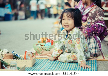 Loei,Thailand - January 1,2016:A girl waiting for give alms to a Buddhist monk  On New Year's Day at the Chiang Khan in Loei. - stock photo