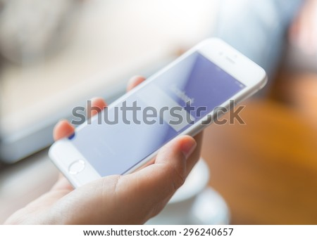 Loei, Thailand - July 12, 2015: Hand holding Iphone with mobile application for Facebook on the screen