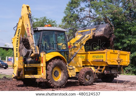 LOEI.THAILAND.JUNE.16.2015: Heavy yellow excavator with shovel standing during earth moving to the truck works outdoors on the site in Thailand.Jun, 16, 2015.