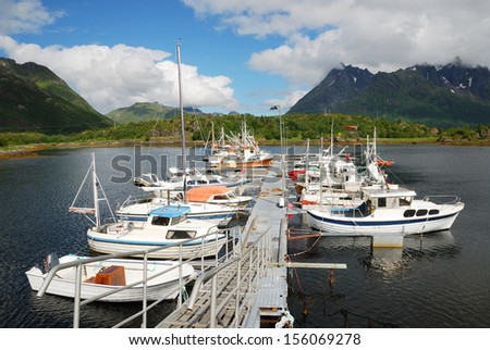 Lofoten is an archipelago. Various boats, yachts and motorboats are moored at the small pier in the fjord. In the background there are majestic mountains overgrown with greenery. - stock photo