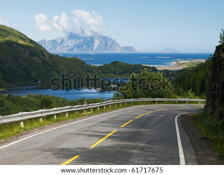 Lofoten landscape with rocky shore and asphalt road, Norway