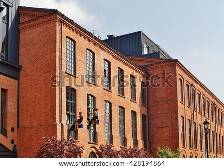 Loft Aparts ,Lodz,Poland - Revitalized buildings - windows cleaners working on chair on  building