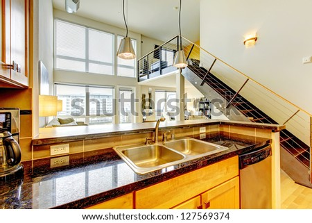 Loft modern bright apartment with wood kitchen and staircase. - stock photo