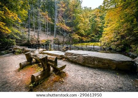 Log bench overlooking a small pond at Oregon Ridge in early Autumn where hikers rest - stock photo