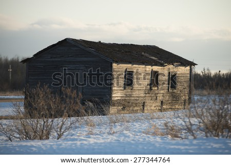 Log cabin in snow covered field at Hecla Grindstone Provincial Park, Manitoba, Canada - stock photo