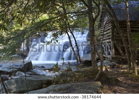 Log cabin in woods with waterfall