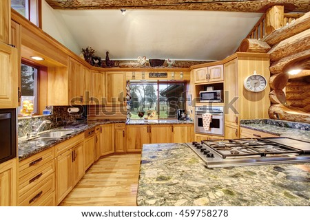 Log cabin kitchen interior design with large honey color storage combination and kitchen island with stone counter top. Northwest, USA