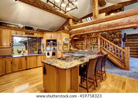 Log cabin kitchen interior design with large honey color storage combination and kitchen island with stone counter top. View of staircase. Northwest, USA