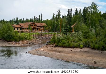 Log Home along the river in Alaska near Fairbanks - stock photo