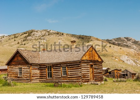 Log home in the ghost town/state park of Bannack in Montana.  The small buildings in the back are Bachelors Row. The middle window of this home may have a ghost looking at you! - stock photo