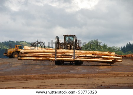 Log loader working a lumber mill logging truck receiving yard in Roseburg Oregon - stock photo