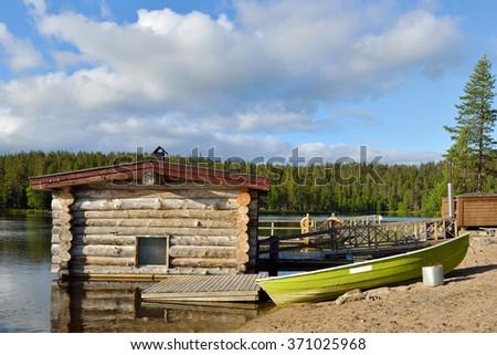 Log sauna on shore of lake. Landscape with boat - stock photo
