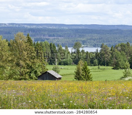 Log, timber barn, meadows this side the farmland, woodland landscape. Great-Lake down in the valley. - stock photo