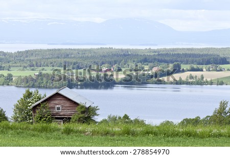 Log, timber barn this side the farmland, landscape. Great-Lake and mountains in the background. - stock photo