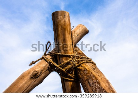 Log tripod in the field to hanging pot - stock photo