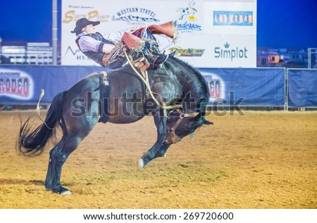 LOGANDALE , NEVADA - APRIL 10 : Cowboy Participating in a Bucking Horse Competition at the Clark County Fair and Rodeo a Professional Rodeo held in Logandale Nevada , USA on April 10 2015 - stock photo