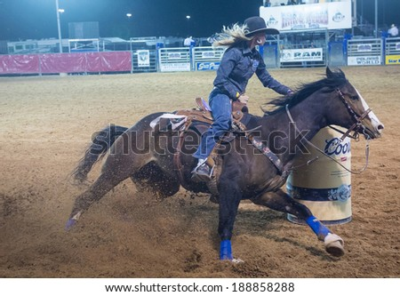 LOGANDALE , NEVADA - APRIL 10 : Cowgirl Participating in a Barrel racing competition in the Clark County Fair and Rodeo a Professional Rodeo held in Logandale Nevada , USA on April 10 2014 - stock photo