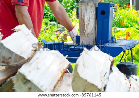 logger make firewood with an electric splitter - stock photo