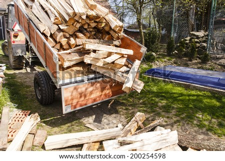 logging tractor on the back yard - wood for fire - stock photo